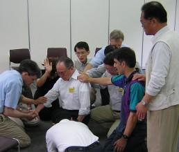 重荷を負っていた兄弟のために祈っているグループの姿
