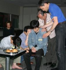 重荷を負っていた兄弟のために祈っている数人